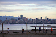 Beach volleyball at Jericho Beach. Downtown Vancouver's Skyline across Burrard Inlet, at sunset.