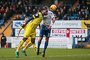 Chey Dunkley (Oxford United) heads the ball behind under pressure from Tom Pope (Bury) for a corner to Bury during the EFL Sky Bet League 1 match between Bury and Oxford United at the JD Stadium, Bury, England on 17 December 2016. Photo by Mark P Doherty.