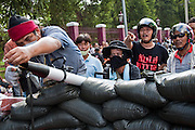 14 MAY 2010 - BANGKOK, THAILAND: Anti government protesters fire small rockets at Thai military helicopters near the intersection of Rama IV and Witthayu Roads in Bangkok Friday morning. The protesters used stolen water canon tubes to increase their accuracy. Tensions among Red Shirt protesters demanding the dissolution of the current Thai government rose overnight after Seh Daeng, the Red Shirt's unofficial military leader was shot in the head by a sniper. Gangs of Red Shirts have taken over military checkpoints on Rama IV and are firing small rockets at military helicopters and army patrols in the area. Troops have responded by firing towards posters.  PHOTO BY JACK KURTZ