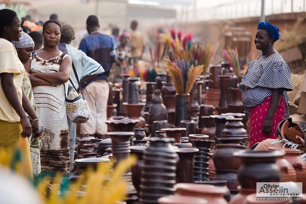A woman selling pottery greets customers at the 22nd Salon International de l'Artisanat de Ouagadougou (SIAO) in Ouagadougou, Burkina Faso on Saturday November 1, 2008.