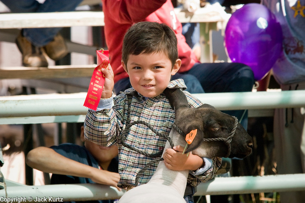 09 SEPTEMBER 2004 - WINDOW ROCK, AZ: A Navajo boy shows off the ribbon he won during the market lambs competition at the 58th annual Navajo Nation Fair in Window Rock, AZ. The Navajo Nation Fair is the largest annual event in Window Rock, the capitol of the Navajo Nation, the largest Indian reservation in the US. The Navajo Nation Fair is one of the largest Native American events in the United States and features traditional Navajo events, like fry bread making contests, pow-wows and an all Indian rodeo.  PHOTO BY JACK KURTZ