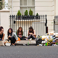 London, UK - 27 August 2012: people sit on the floor near rubbish during the annual Notting Hill Carnival.