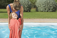 Mother embracing daughter (5-6) wrapped in towel by pool