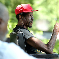 Michael Neal, a homeless resident in Tupelo sits in the shade as he smokes his cigarette as he talks with Perry Burkart.