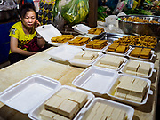 "14 FEBRUARY 2019 - SIHANOUKVILLE, CAMBODIA: A Chinese woman sells tofu in the Leu Market in Sihanoukville. There are thousands of Chinese workers in Sihanoukville who work to support the casino and hotel industry in the town. There are about 80 Chinese casinos and resort hotels open in Sihanoukville and dozens more under construction. The casinos are changing the city, once a sleepy port on Southeast Asia's ""backpacker trail"" into a booming city. The change is coming with a cost though. Many Cambodian residents of Sihanoukville  have lost their homes to make way for the casinos and the jobs are going to Chinese workers, brought in to build casinos and work in the casinos.      PHOTO BY JACK KURTZ"