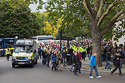 Police vans follow the fans down Park Lane during the Football Lads Alliance march between Park Lane and Westminster Bridge, London on 7 October 2017. Photo by Phil Duncan.