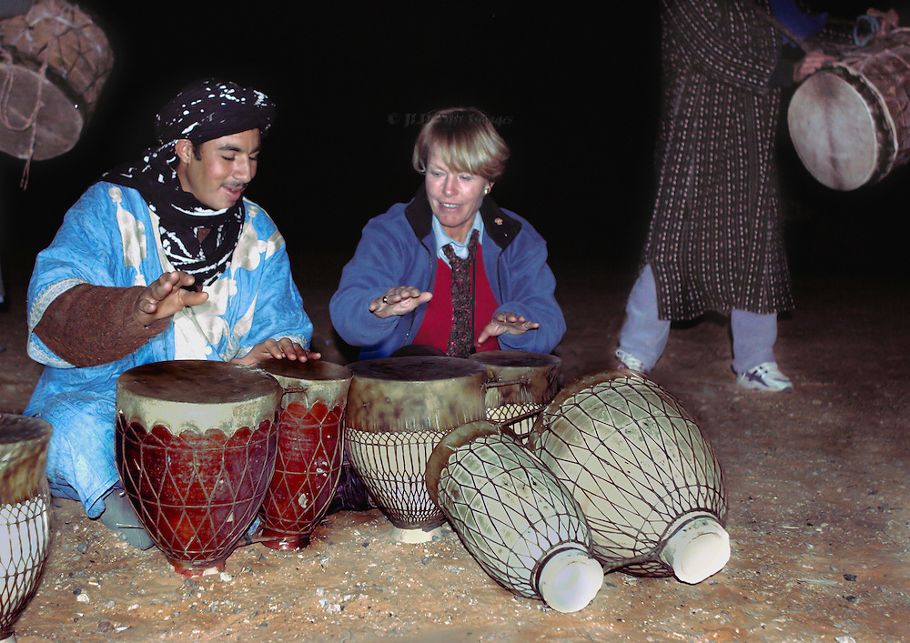 Berber drummer teaches drumming to a blonde American tourist, at night, by firelight, in the Sahara desert.