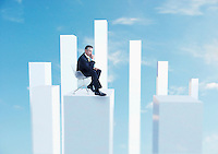 Business man sitting in chair on white pillar digital composite