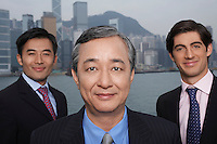 Portrait of three business men office buildings in background