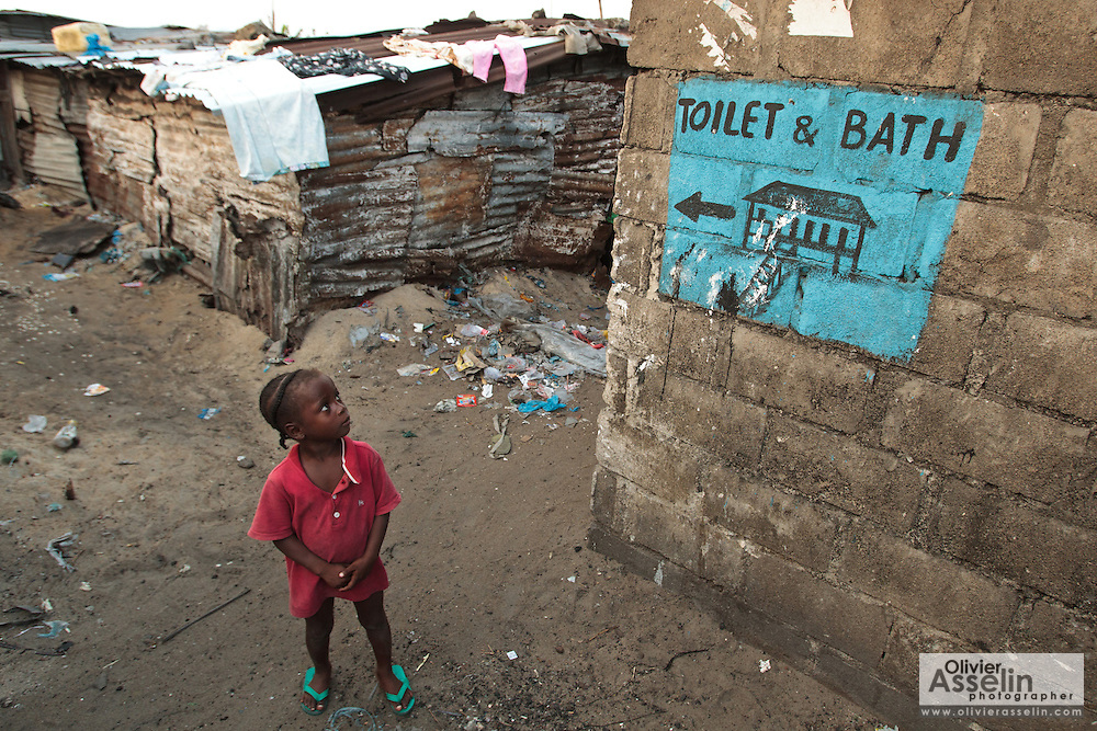 A girl stands under a painting that indicates directions to a nearby toilet and bath facility in the West Point slum in Monrovia, Montserrado county, Liberia on Monday April 2, 2012.
