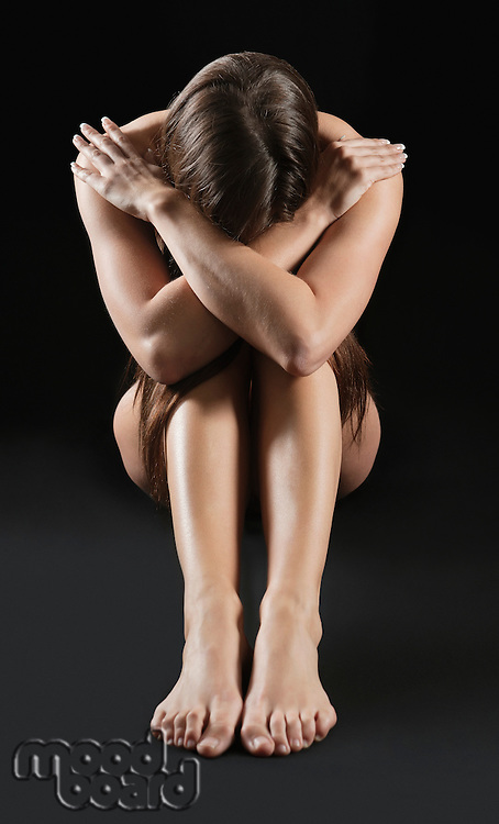 Depressed young woman sitting naked with head down over black background