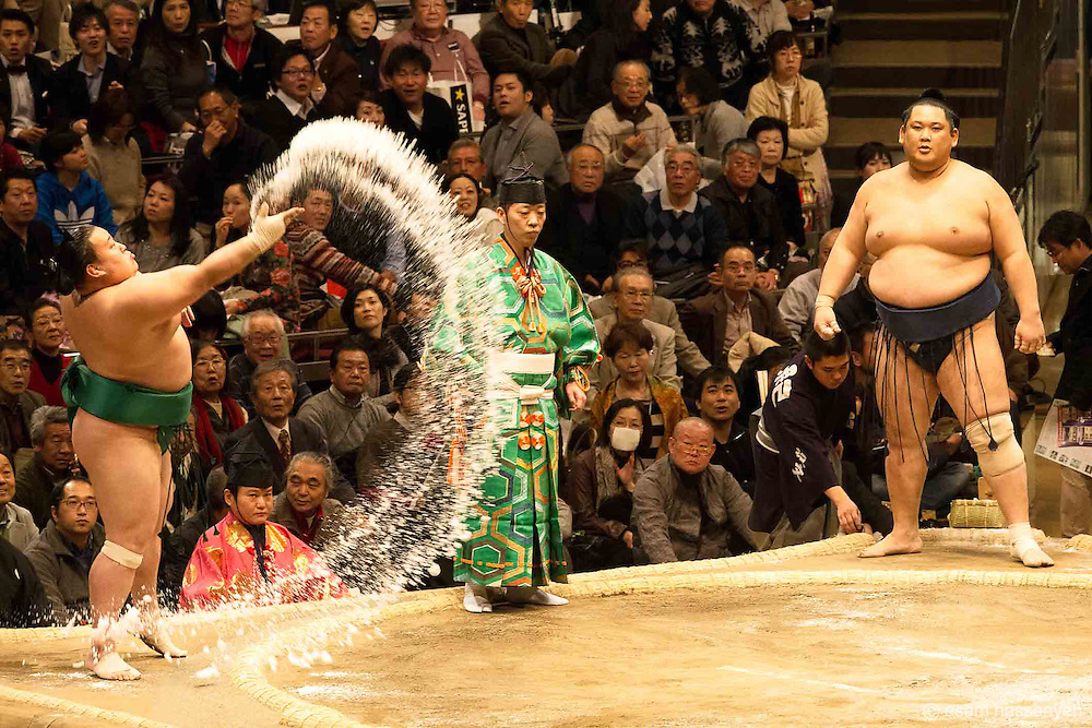 A Sumo throws salt into the ring before a bout  at the Ryōgoku Kokugikan in Tokyo during the grand tournament.<br /> <br /> This is a ritual performed by every Sumo before he fights to ward of bad spirits and give him good fortune.