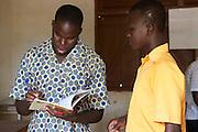 A teacher marks a students school work, Ghana.