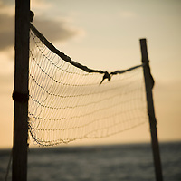 shallow depth view of Volleyball net silhouetted at sunset near ocean