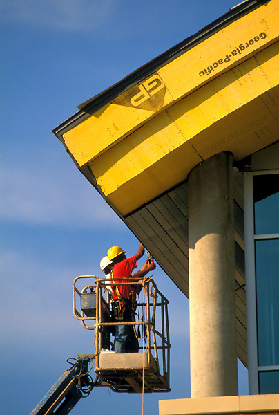 Stock photo of workmen in a lift  installing fascia board and insulation during construction in Houston, Texas.