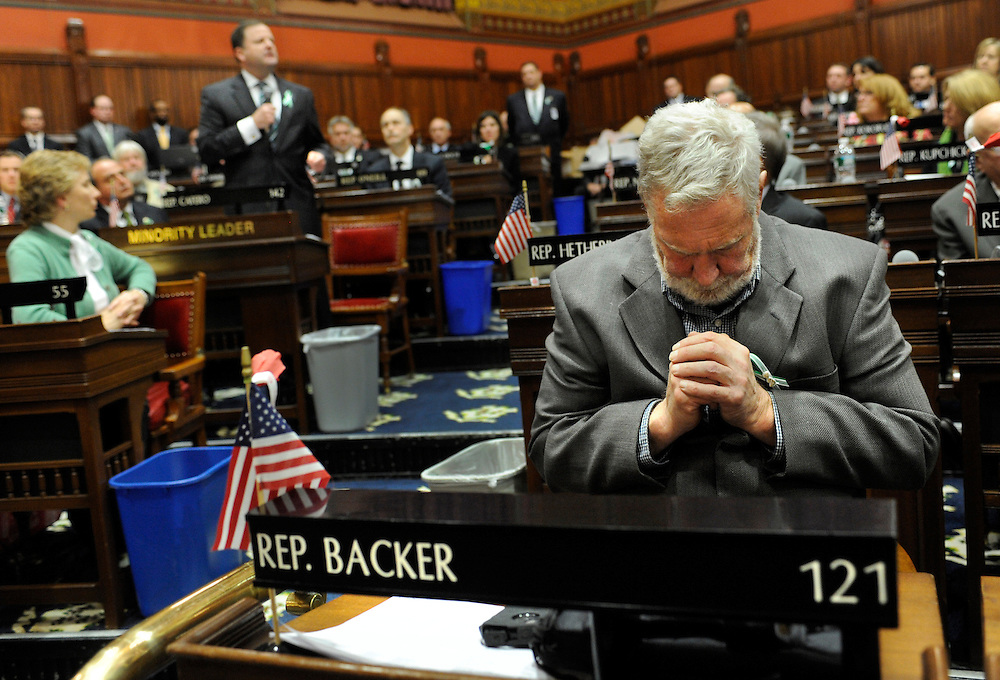 State Rep. Terry Backer, D-Stratford, right, bows his head as State Sen. John McKinney, R-Fairfield, left, addresses the House of Representatives and Senate as they meet together at the state Capitol for a memorial service for the victims of the Sandy Hook Elementary School shooting before a special session in Hartford, Conn., Wednesday, Dec. 19, 2012. (AP Photo/Jessica Hill)
