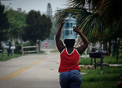 September 9, 2017 - Florida, U.S. - A woman carries a large jug of water on her head in Lantana Saturday morning, September 9, 2017 in advance of Hurricane Irma. (Credit Image: © Bruce R. Bennett/The Palm Beach Post via ZUMA Wire)