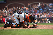 San Francisco Giants catcher Buster Posey (28) lays on the ground after a play at home plate against the Philadelphia Phillies at AT&T Park in San Francisco, California, on August 20, 2017. (Stan Olszewski/Special to S.F. Examiner)