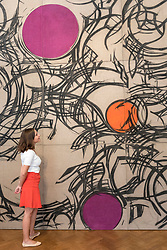 "© Licensed to London News Pictures. 25/06/2018. LONDON, UK. A staff member views an artwork by Wanda Czelkowska. Preview of ""Lands of Lads, Land of Lashes"", an exhibition of sculptures and paintings by three female artists of the1960s and 1970s - Rosemarie Castoro, Wanda Czelkowska and Lydia Okumura - specialising in Minimal and Post-Minimal art.  The exhibition, held at Galerie Thaddaeus Ropac in Mayfair, runs 25 June to 11 August 2018.  Photo credit: Stephen Chung/LNP"