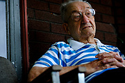 "Achille (Kelly) Gasbarra, sits on his front porch in New Kensington, Pa. Gasbarra, who recently celebrated his 75th wedding anniversary with his wife, was drafted into the Navy as a cook in 1943. He claims to be ""the only guy in the Navy that never saw water,"" sinces he worked in Nevada at a naval ammunition depot.<br /> <br /> New Kensington, a small city located twenty miles northeast of Pittsburgh, is known as the ""Birthplace of the Aluminum Industry"" since it was where the Aluminum Company of America's (ALCOA) first facility was built in 1891. ALCOA presence drove the area's economy for over sixty years.<br /> <br /> When ALCOA closed its New Kensington operations in 1971, 3,300 jobs were lost – a fifth of the local population. As a result,  property values rapidly declined and many homeowners became underwater on their mortgages.<br /> <br /> The population shrank nearly in half, from 26,000 in the early 1970s to about 14,000. Businesses moved to malls or suburban commercial strips and the buildings that previously housed them fell into decay and the city's tax revenues plummeted."