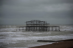 © Licensed to London News Pictures. 15/09/2015. Brighton, UK. The old Brighton Pier surrounded by grey skies and rough seas as high winds and heavy rain batter Brighton seafront on  the south coast of England.  Photo credit: Ben Cawthra/LNP