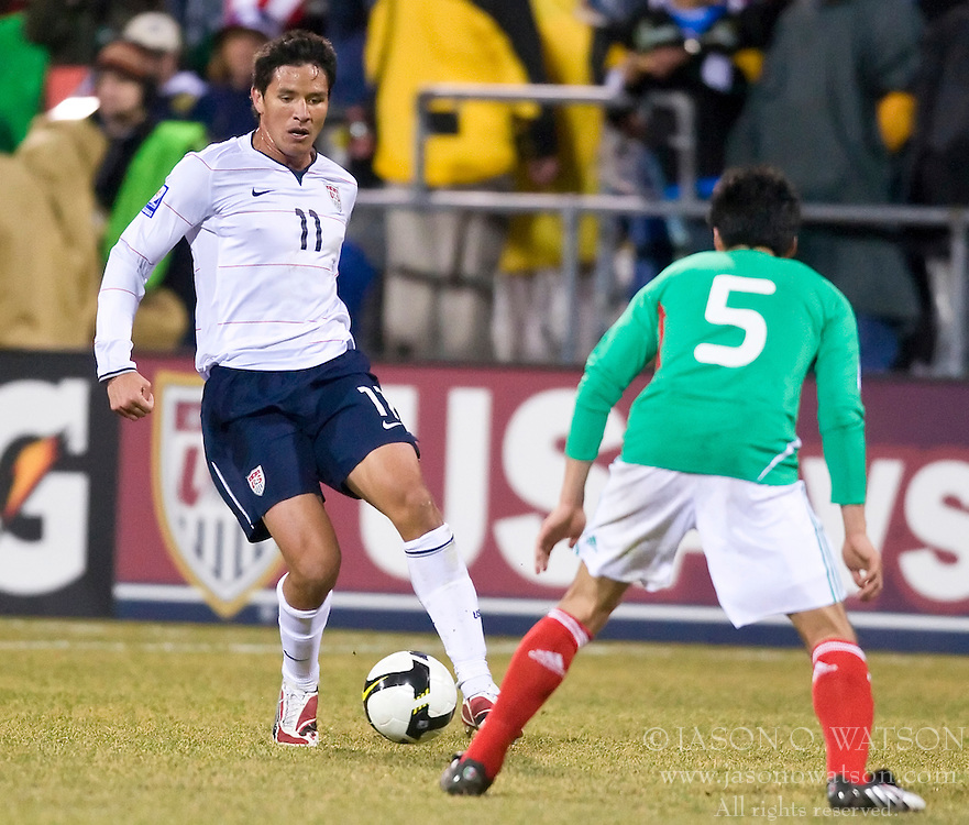United States forward Brian Ching (11) is defended by Mexico defender Ricardo Osorio (5).  The United States men's soccer team defeated the Mexican national team 2-0 in CONCACAF final group qualifying for the 2010 World Cup at Columbus Crew Stadium in Columbus, Ohio on February 11, 2009.