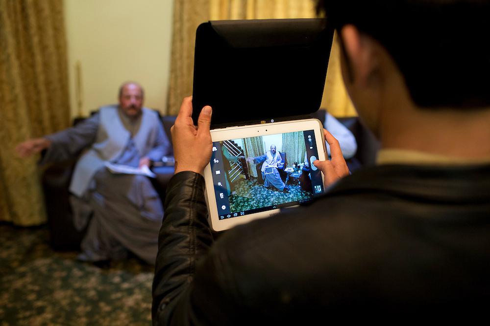 March 23, 2014 - Kandahar, Afghanistan - Hashmat Karzai, cousin of Afghan President Hamid Karzai at his home in their historic village of Karz near Kandahar, Afghanistan. <br /> An assistant takes a photo of Karzai.