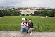 Foreign tourists take a selfie with a background of Schloss Schonbrunn, in Vienna, Austria, EU.
