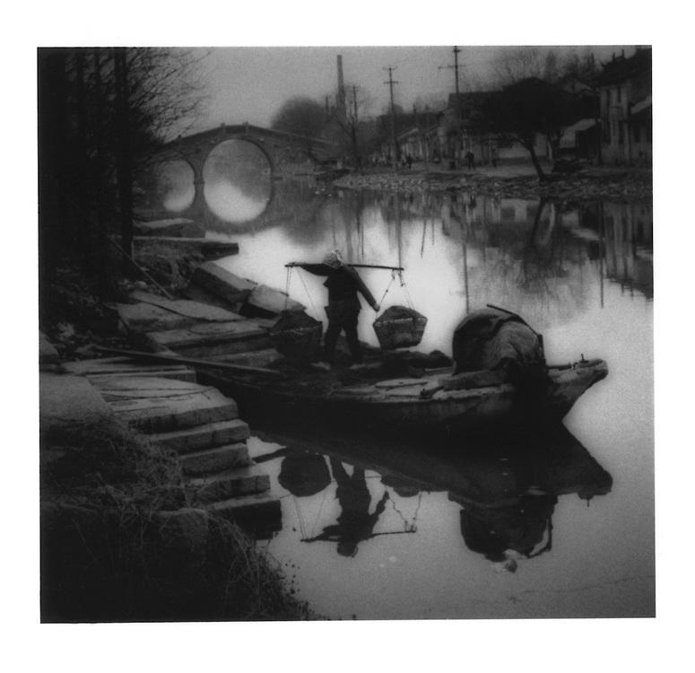 Unloading coal from a canal barge.  Near Suzhou, Jiangsu Province, China.  1996