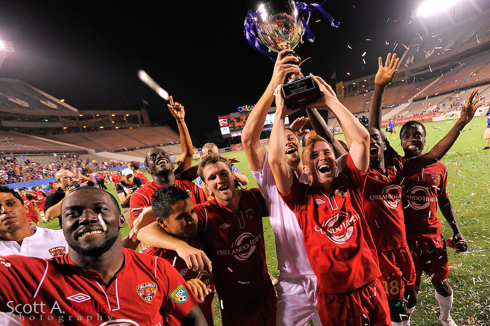 Orlando City forward Jamie Watson (77) hoists the trophy with his teammates after the Lions 4-0 win over the Charleston Battery at the Florida Citrus Bowl on July 27, 2012 in Orlando, Florida. The win clinched the USL-Pro regualr season title for Orlando...©2012 Scott A. MIller)..