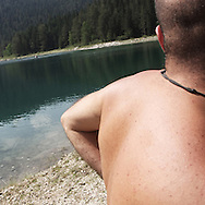 a man near a Dorumitor lake. There are several arguments about the derivation of the name  &quot;Montenegro&quot;, one of these relates to dark and deep forests  that once covered the Dinaric Alps, as it was possible to see them from the sea. <br /> Mostly mountainous with 672180 habitants on an area of 13812 Km&sup2;, with a population density of  48 habitants/Km&sup2;. <br /> It borders with Bosnia, Serbia, Croatia, Kosovo and Albania but  Montenegro has always been alien to the bloody political events that characterized Eastern Europe in recent decades. <br /> From 3 June 2006, breaking away from Serbia, Montenegro became an independent state. <br /> In the balance between economy devoted to sheep farming and a shy tourist, mostly coming from Bosnia and Herzegovina, Montenegro looks to Europe with a largely unspoiled natural beauty. <br /> Several cities in Montenegro, as well as the park Durmitor, considered World Heritage by UNESCO but not yet officially because Montenegro has yet to ratify the World Heritage Convention of UNESCO.