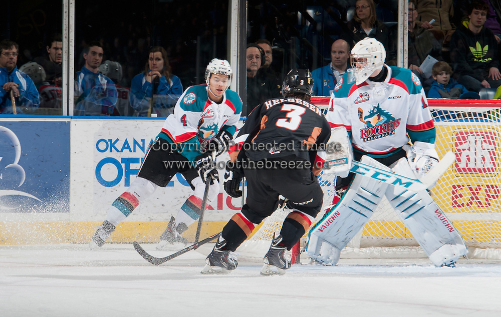 KELOWNA, CANADA - FEBRUARY 28: Kenton Helgesen #3 of Calgary Hitmen checks Madison Bowey #4 as he skates behind the net of Jackson Whistle #1 of Kelowna Rockets during the second period on February 28, 2015 at Prospera Place in Kelowna, British Columbia, Canada.  (Photo by Marissa Baecker/Shoot the Breeze)  *** Local Caption *** Madison Bowey; Jackson Whistle; Kenton Helgesen;