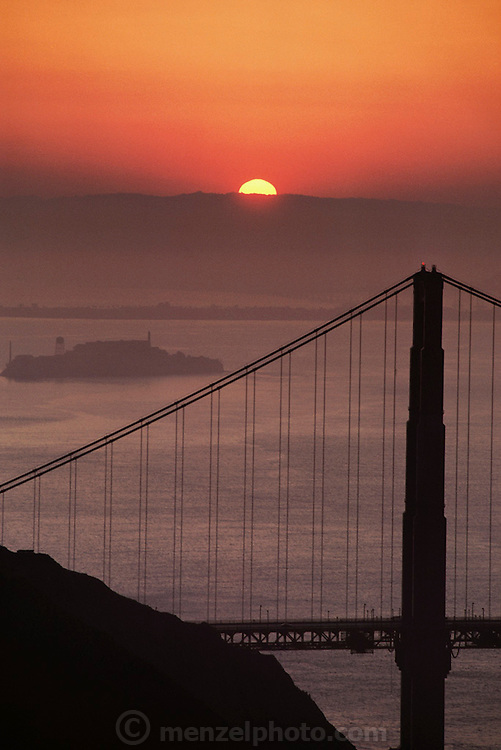 North tower of the Golden Gate Bridge at sunrise; Alcatraz is seen in the background on the left. San Francisco, California. Construction of the bridge began in January 1933 and was completed in April 1937.