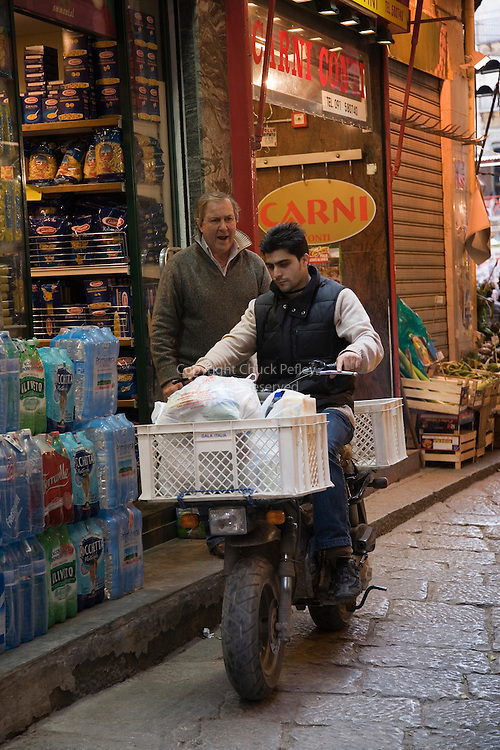 Shop owner gives instructions to delivery boy on motorscooter at Vucciria Market, Palermo, Sicily, Italy