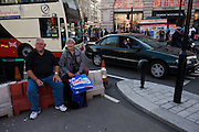 Two middle-aged shoppers sit on a street barrier in the middle of Piccadilly Circus, surrounded by busy traffic.