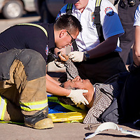020113       Cable Hoover<br /> <br /> Gallup firefighter Fabian Tom, left, holds the head of an injured pedestrian as other emergency workers prepare to put a neck brace on the man who was run over by a truck at the intersection of Historic Highway 66 and Second Street in downtown Gallup Friday.