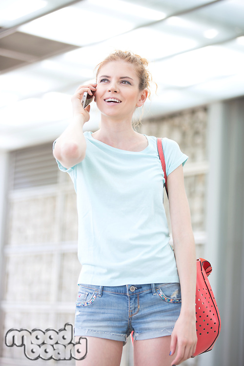 Happy woman looking away while using cell phone outdoors