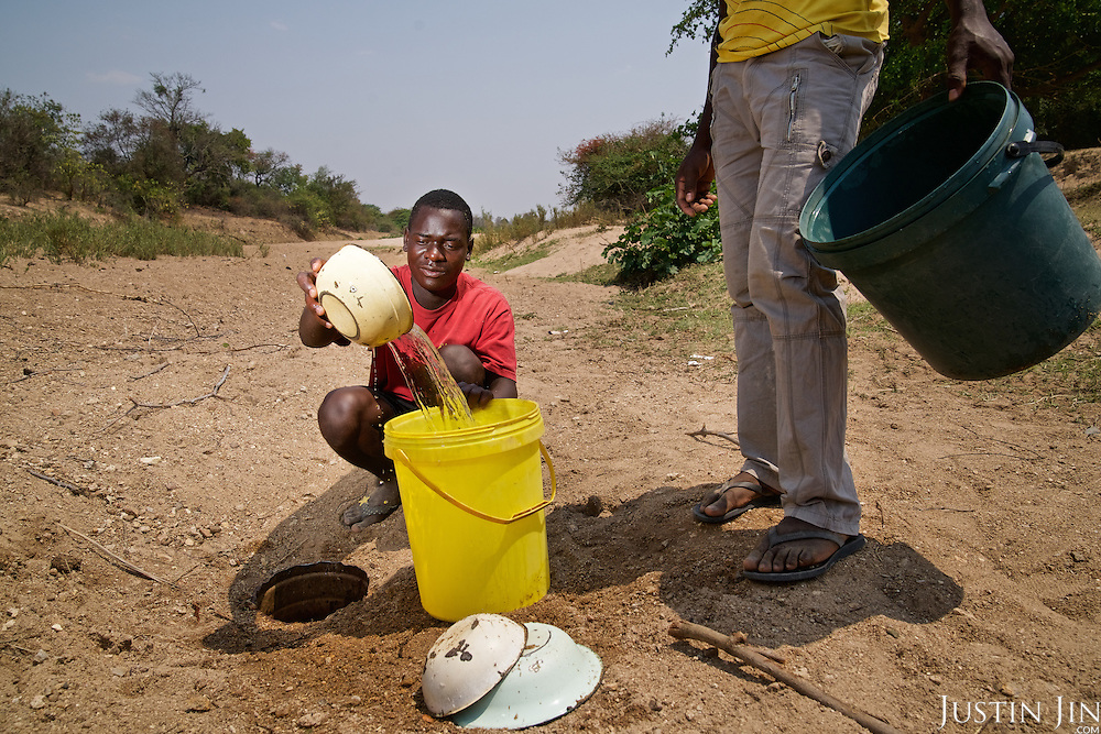 Two men collect water from a hole dug into a dried riverbed in drought-hit Masking Province, Zimbabwe.  <br /> <br /> Untreated and untested, the shallow stagnant water is a potential source of pollutants and water-borne diseases. <br /> <br /> Drought in southern Africa is devastating communities in Zimbabwe, leaving 4 million people urgently in need of food aid. The government declared a state of emergency,. <br /> <br /> Here in Masvingo Province, the country's hardest hit province, vegetation has wilted, livestock is dying, and people are at serious risk of famine. <br /> <br /> Pictures shot by Justin Jin