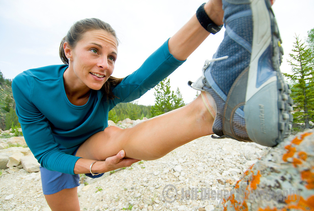 A young woman stretches before a trail run in Jackson Hole, Wyoming.