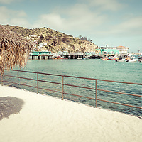 Catalina Island tiki umbrella retro photo with the Catalina Casino, Avalon Pier, and Avalon Harbor. Beautiful Santa Catalina Island is a popular travel destination off the Southern California coast. Photo is high resolution. Copyright ⓒ 2017 Paul Velgos with All Rights Reserved.