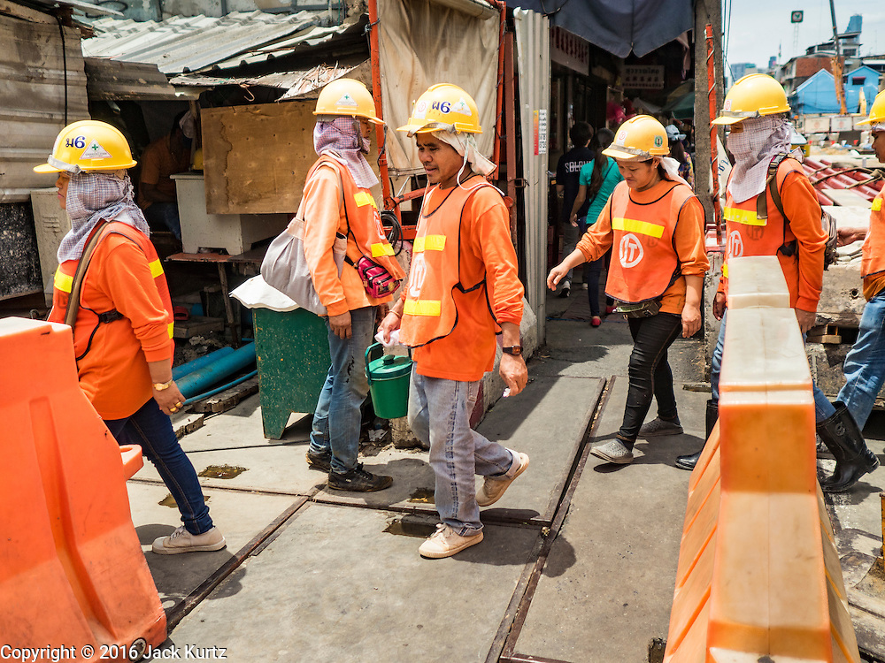 08 JUNE 2016 - BANGKOK, THAILAND:  Workers building the new subway station at the intersection of Phlap Phla Chai and Chareon Krung Streets in Bangkok's Chinatown neighborhood walk to lunch. The Bangkok Metropolitan Rapid Transit (MRT) system, Bangkok's subway, is being expanded through Chinatown and a station is under construction at the intersection. The small produce market at the intersection will have to move and several of the businesses near the intersection have been evicted to make way for the construction. Bangkok's Chinatown, considered by some to be one of the best preserved Chinatown districts in the world, is changing. Many of the old shophouses are being demolished and replaced by malls and condominium developments.     PHOTO BY JACK KURTZ