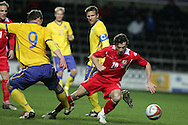 Simon Davies of Wales is tackled by Sweden's Kim Kallstrom (9). International friendly, Wales v Sweden at the Liberty Stadium in Swansea on Wed 3rd March 2010. pic  by  Andrew Orchard