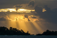 The suns rays push through storm clouds at dawn over St Joseph Atoll, D'Arros Island and St Joseph Atoll, Amirantees, Seychelles,