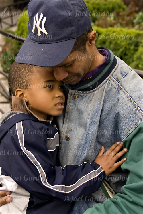 African American father sitting on bench holding his young son affectionately, displaying caring and love.<br /> <br /> Release #2307