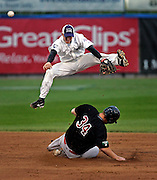 SCOTT MORGAN | ROCKFORD REGISTER STAR.The RiverHawk's Jono Brooks (11) jumps over Kalamazoo's Tim Brown (34) slides into second in the middle of a double play to end the third-inning Friday, July 17, 2009, during their game at Road Ranger Stadium in Loves Park.