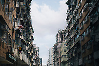 Residential buildings fill the sky in an alleyway in Kowloon.
