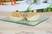 two halves of boiled eggs stuffed with chickpea filling side view close-up on rustic tablecloth and glass dish with a small fork between half eggs on blurred background
