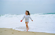 An eight year old girl running out of the sea during a holiday in France