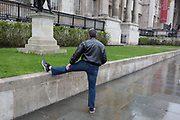 A man stretches a stiff leg beneath the columned architecture of the National Gallery in Trafalgar Square, Westminster, on 9th April 2019, in London, England.