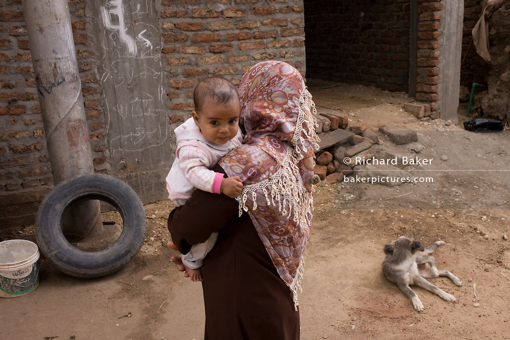 A local mother holds her youngest child in Bairat, a village on the West Bank of Luxor, Nile Valley, Egypt.